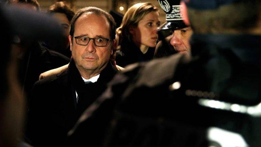 Le président français François Hollande (G) regarde un officier de police lors d'une visite du dispositif de sécurité mis en place pour le nouvel an à Paris le 1er janvier 2016