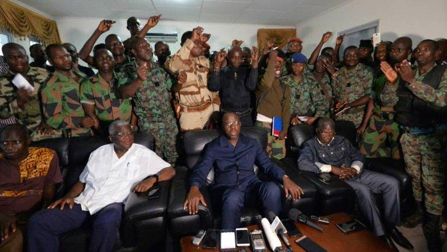 Une délégation de soldats rebelles se tiennent derrière le ministre ivoirien de la Défense Alain Richard Donwahi (C) après des négociations, le 7 janvier 2017 à Bouaké