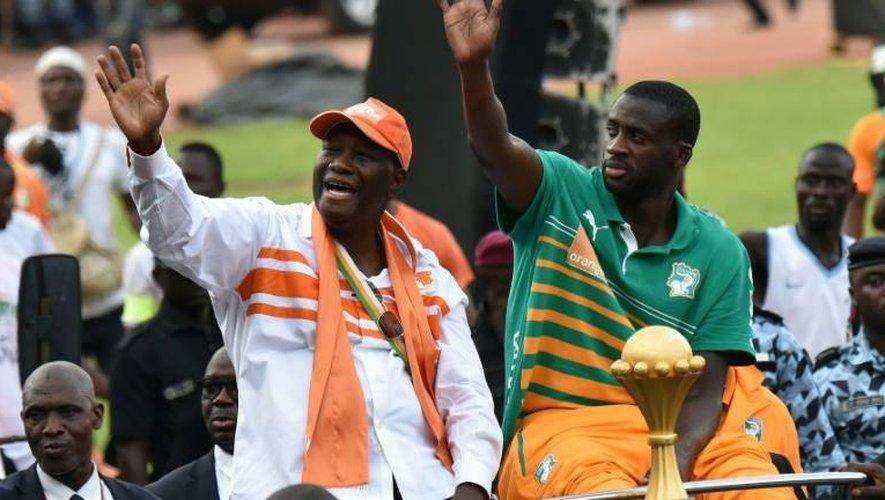 Le président ivoirien Alassane Ouattara avec le capitaine de l'équipe nationale Yaya Touré et le trophée de la CAN-2015, le 9 février 2015 à Abidjan
