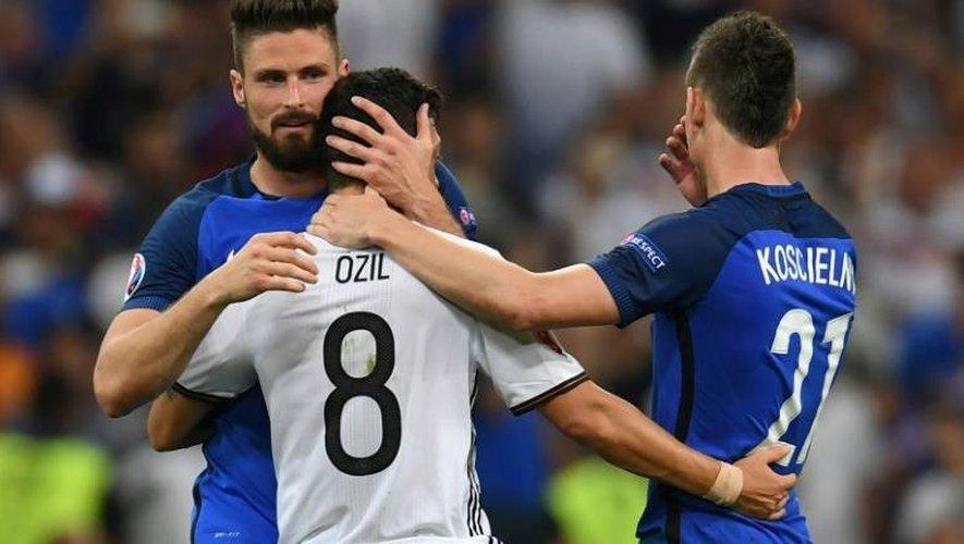 Le Français d'Arsenal Olivier Giroud et Laurent Koscielny consolent leur coéquipier allemand Mesut Özil après la demi-finale de l'Euro-2016, remportée 2-0 par les Bleus, le 7 juillet 2016 au Vélodrome de Marseille