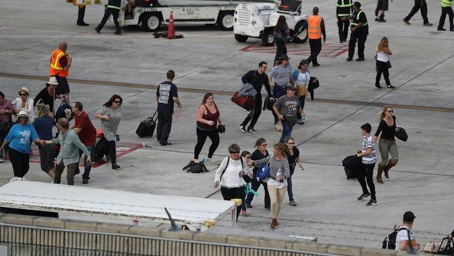 Des voyageurs fuient pour se mettre à l'abri sur le tarmac de l'aéroport de Lauderdale-Hollywood après une fusillade mortelle, le 6 janvier 2017