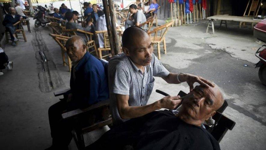 Un barbier en activité près de la célèbre maison de thé de Chengdu, le 11 septembre 2016