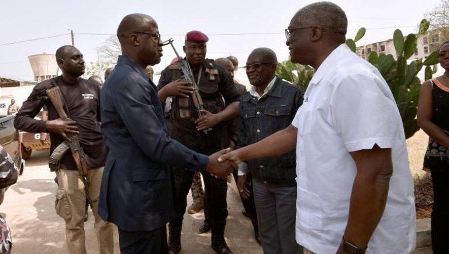 Poignée de mains entre le ministre ivoirien de la Défense Alain-Richard Donwahi (g) et le maire de Bouaké Issoufou Nicolas Djibo, le 7 janvier 2017 à Bouaké
