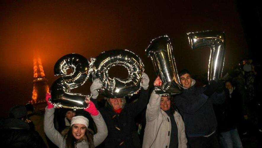 Des personnes célèbrent le Nouvel an au pied de la Tour Eiffel le 1er janvier 2017 à Paris