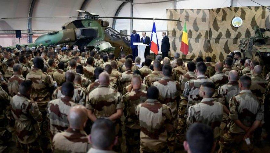 François Hollande (C), le Premier ministre malien Modibo Keita (G) et le ministre de la Défense française Jean-Yves Le Drian (D), face aux troupes de l'opération Barkhane à Gao, dans le nord du Mali, le 13 janvier 2017