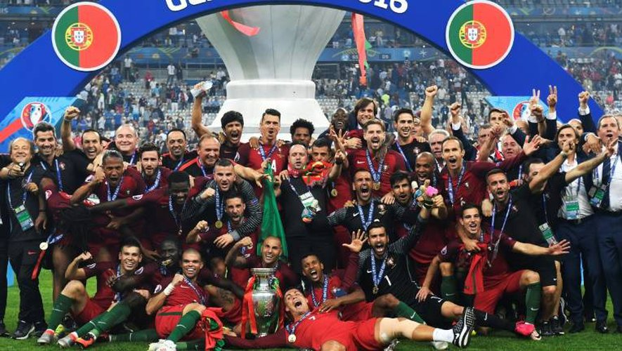 Les joueurs et personnels de l'équipe de football portugaise posent avec le trophée après avoir remporté la finale de l'Euro-2016, le 10 juillet 2016 au Stade de France, à Saint-Denis, près de Paris