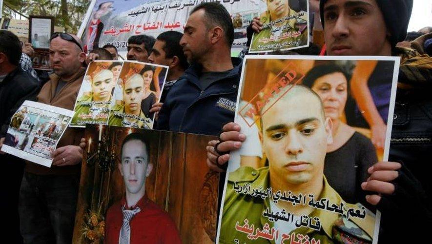 Des portraits du soldat israélien Elor Azaria (d) et du Palestinien Abdul Fatah al-Sharif brandis lors d'une manifestation le 4 janvier 2017 à Hébron, en Cisjordanie