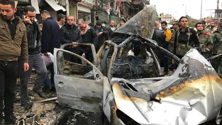 Des Syriens sur le lieu de l'explosion à Jablé (ouest), un fief du régime, d'une voiture piégée qui a fait 15 morts, essentiellement des civils, selon l'Observatoire syrien des droits de l'Homme (OSDH), le 5 janvier 2017