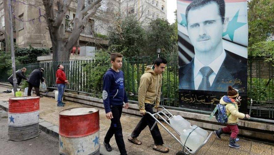 Des Syriens remplissent des bonbonnes d'eau de la fontaine à Damas, le 3 janvier 2017