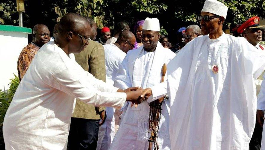 Une photo fournie par la présidence nigérienne le 13 janvier 2017, montre le président nigérian Muhammadu Buhari (D) serrant la main du nouveau président élu de Gambie, Adama Barrow (G), en présence du président gambien Yahya Jammeh (C) à Banjul