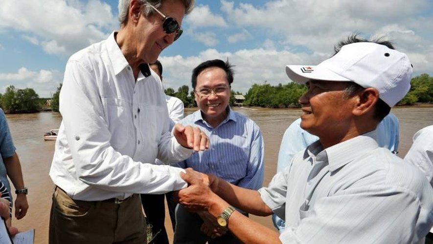 Le secrétaire d'Etat américain John Kerry sert la main de l'ancien guerillero Vo Van Tam le 14 janvier 2017 sur le delta de la rivière du Mekong