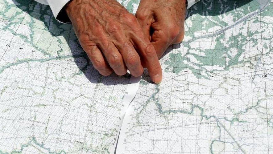Le secrétaire d'Etat américain John Kerry montre l'endroit où s'est déroulée une bataille au Vietnam qui a valu d'être décoré, au moment d'une descente en bateau sur le delta de la rivière du Mekong, le 14 janvier 2017