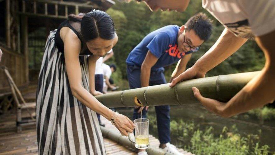 De l'alcool s'écoule dans un verre, après avoir veilli plusieurs années dans un tronc de bambou, le 30 juillet 2016 à Yibin, en Chine