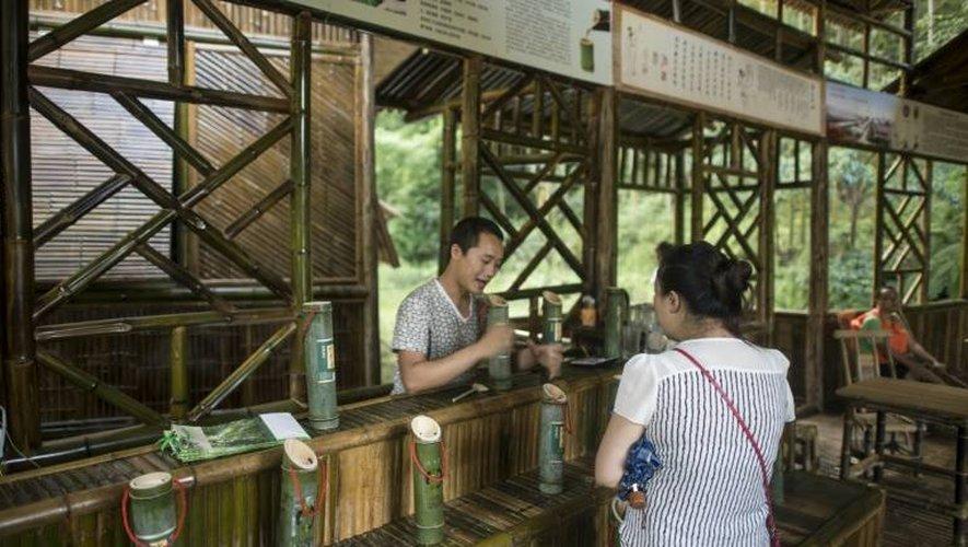 Une touriste achète de l'alcool vieilli dans un tronc de bambou, le 30 juillet 2016 à Vibin