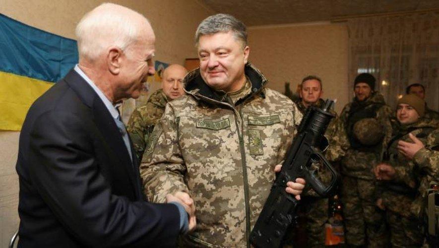 Le président ukrainien Petro orochenko avec le sénateur américain John McCain (g) à Chirokiné, dans l'est séparatiste prorusse de l'Ukraine, le 31 décembre 2016
