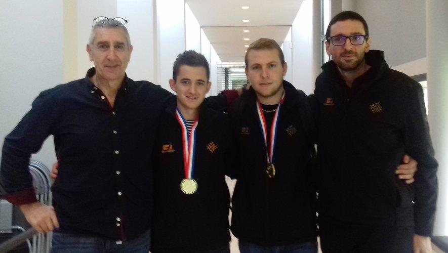 Médailles d'or autour du cou. Baptiste et Louis sont entourés par Jean-Marc Volpelier et Julien Fontanelli, coach de Languedoc-Roussillon.