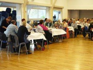 Les aînés ruraux autour de tables bien décorées pour le repas de fin d'année.