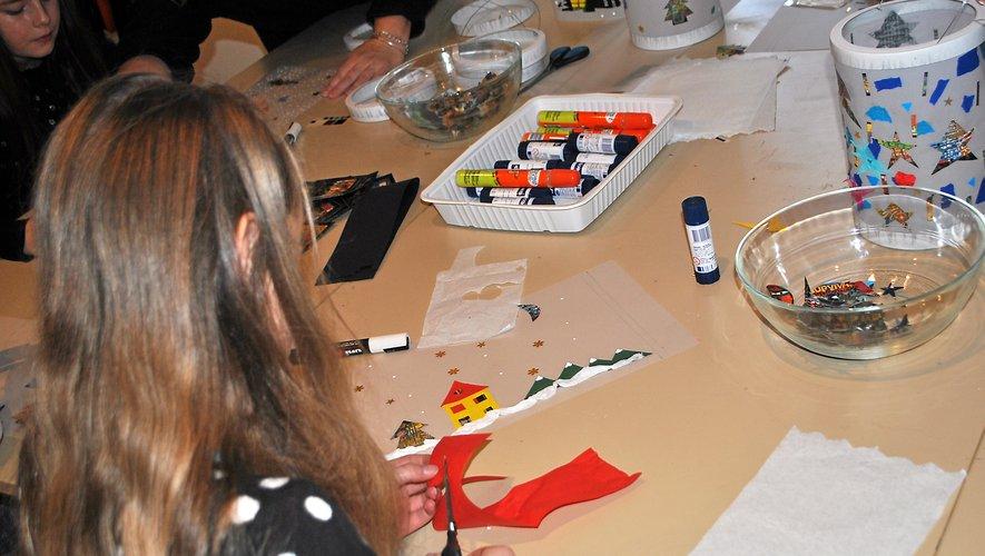 Énora fabrique son lampion sur un calque, avec des motifs rappelant les fêtes de Noël.