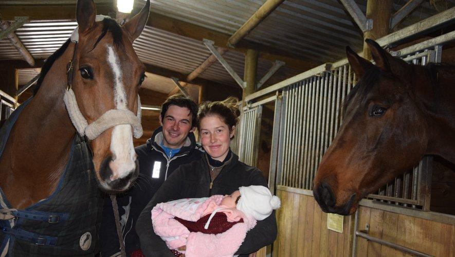 Pierre, Léa, leur nouveau-née Juliette, et Tonnerre à gauche, dans l'écurie en bois.