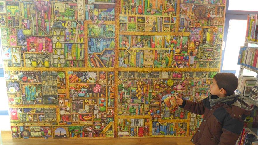 Mathéo, photo d'un détail en mains, cherchant à retrouver l'image sur le puzzle.