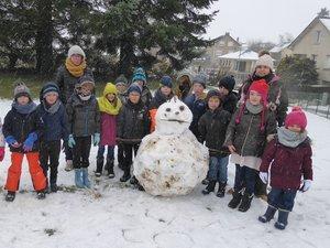 Les enfants devant leur bonhomme de neige, encadrés par Mélanie et Aurélie.