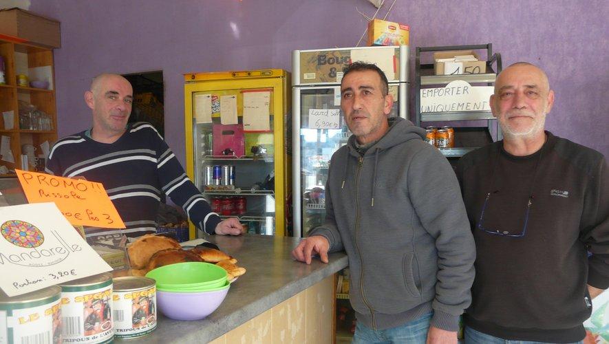 Joël, derrière le comptoir, avec deux de ses clients.