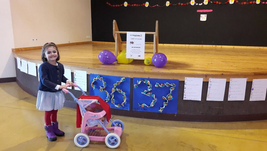 Devant les décors réalisés par les écoles, la petite Aura est fière de raconter qu'elle a participé au Téléthon.