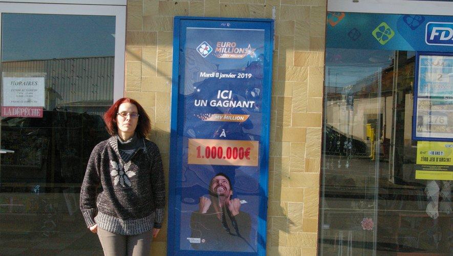 La propriétaire du tabac-presse-loto, Lauriane Vincent,  pose à côté de l'affiche qui immortalise le gain de cet heureux gagnant.