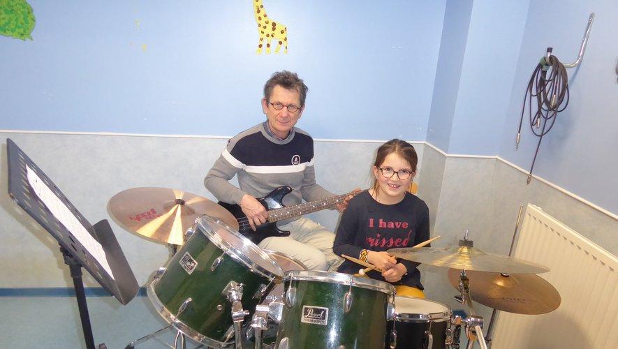 Louise apprenant à jouer de la batterie aux côtés de son professeur Philippe Blanchard.