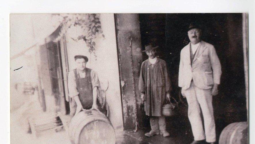 Marius Garrigues à gauche, garçon de cave, avec un client et M. Izard, comptable, devant l'entrée de la cave, rue Combarel.