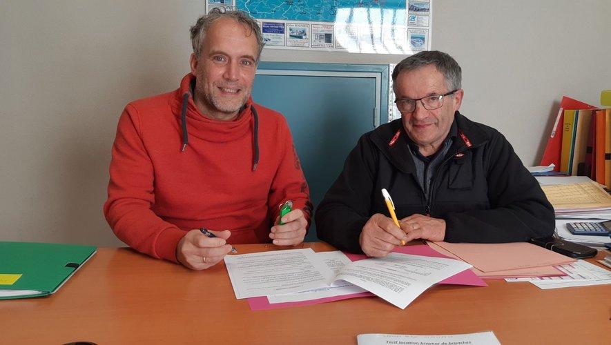 Le maire et Roger Van Stratum en pleine séance de signatures.