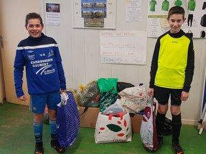 Deux jeunes licenciés U13,Noah Brunet et Pierre Izard, déposant des vêtementsde sport lors de la collecte.