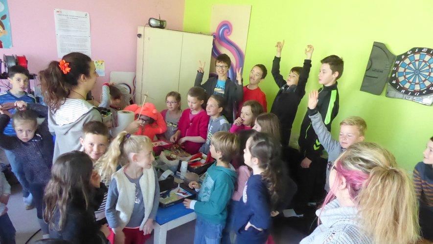 Les enfants participant à la réalisation d'une toupie avec Marion et Justine.