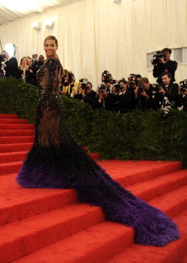 Le glamour est toujours de mise pour Beyoncé en 2012. La chanteuse américaine foule le tapis rouge dans une robe somptueuse faite de transparence, de broderies, et de plumes bicolores. Le tout est signé Givenchy Haute Couture. New York, le 7 mai 2012.