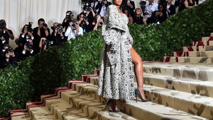 En 2018, Rihanna frappe un grand coup en arrivant au Metropolitan Museum of Art dans une mini robe et un manteau argent brodés de perles et de sequins, accessoirisés d'une mitre. Le tout signé Maison Margiela par John Galliano. New York, le 7 mai 2018.