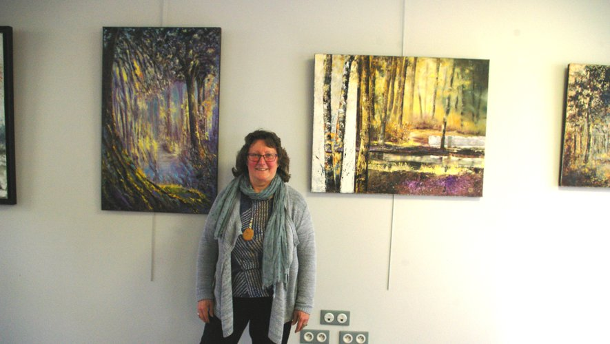 L'artiste pose devant ses toiles.