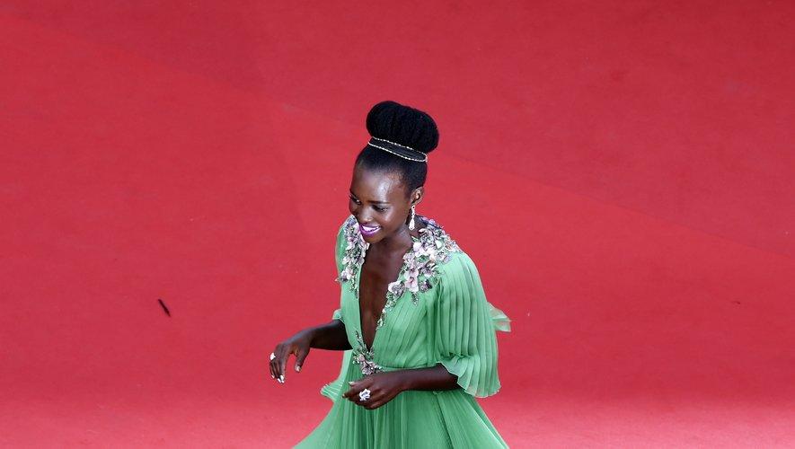 Lupita Nyong'o arborait un look beauté sensationnel sur le tapis rouge cannois en 2015. Elle avait associé un rouge à lèvres rose magenta à un chignon haut régalien magnifié par un bandeau scintillant. Le 13 mai 2015