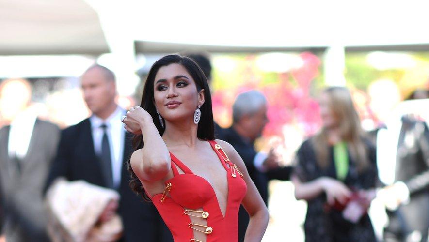 Praya Lundberg a joué la carte de la sexy attitude dans une robe décolletée et fendue, d'un rouge vibrant, ornée d'épingles XXL, signée Versace. Cannes, le 16 mai 2019.
