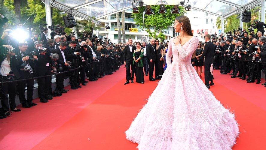 Iris Mittenaere a fait rêver le public cannois dans une sublime robe esprit romantique entièrement recouverte de plumes. Une création déclinée dans un rose délicat, signée Michael Cinco. Cannes, le 22 mai 2019.