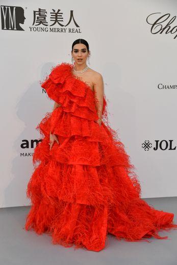 Dua Lipa a fait une arrivée remarquée au gala de l'amfAR dans une robe asymétrique imposante, dans un style romantique, faite de multiples volants. Une création signée Valentino. Cannes, le 23 mai 2019.