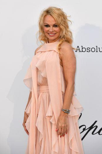 L'actrice américaine Pamela Anderson affichait ses habituelles boucles blondes texturées et une raie sur le côté.