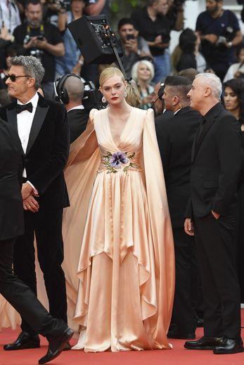 Elle Fanning dans une robe en soie rose tendre et sa cape, par Gucci. Cannes, le 14 mai 2019.
