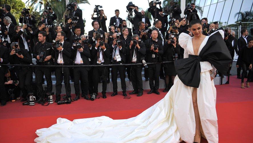 Deepika Padukone dans une robe blanche aux épaules bouffantes ornée d'un noeud noir, par Dundas. Cannes, le 16 mai 2019.