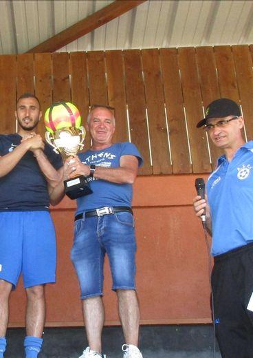Le président (à droite) remet le trophée à Willy gagnant du tournoi