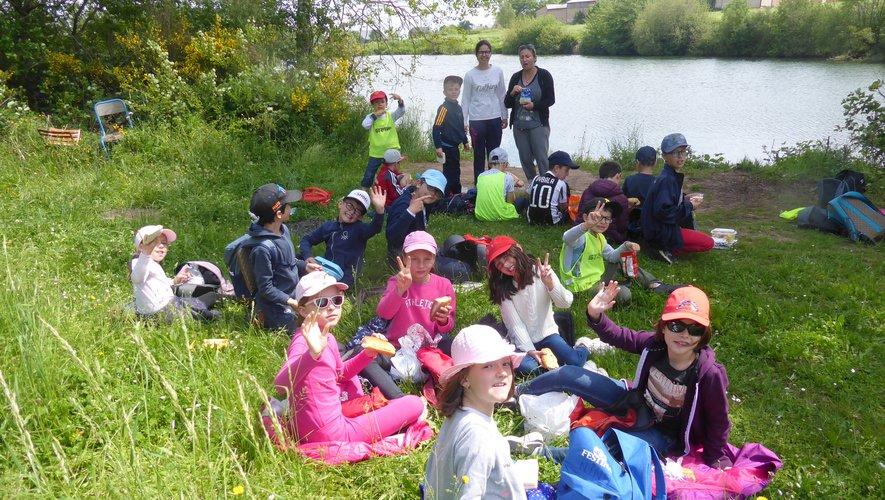 Les participants à cette balade pique-niquant au bord du lac sont encadréspar Marie et Aurélie.