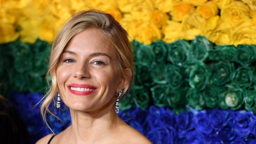 Sienna Miller a opté pour un look estival qui se concentrait sur un teint hâlé resplendissant, un chignon lâche et un brin de rouge à lèvres couleur framboise.
