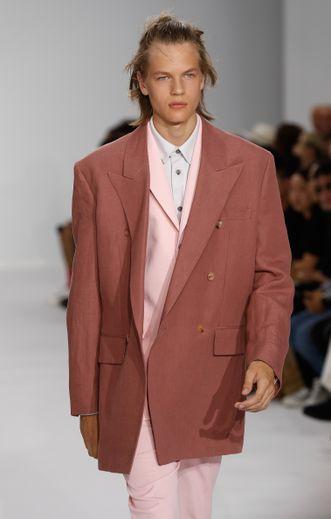 Man bun, mèches rebelles, teint hâlé pour un style soigné chez Paul Smith.