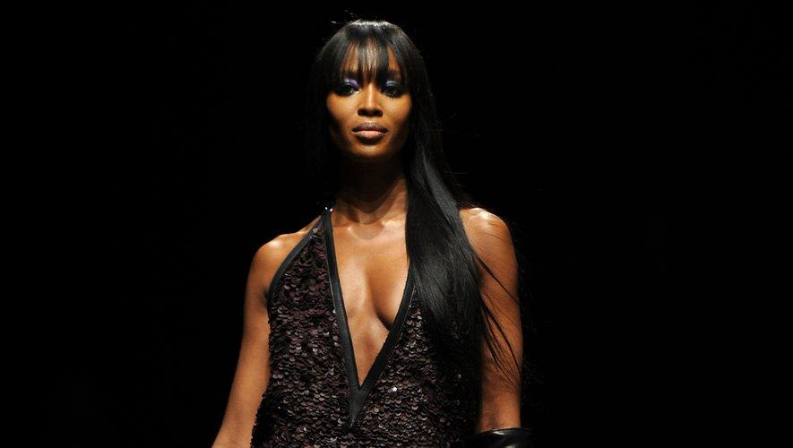 Toujours dans une longue robe qui sublime sa silhouette, Naomi Campbell porte une création issue de la collection automne-hiver 2012-2013 de la maison Roberto Cavalli. Milan, le 27 février 2012.