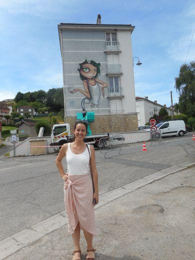 Amélie Vielle, la directrice artistique du festival, avec en fond l'artiste Vinie à l'oeuvre, à Trépalou.