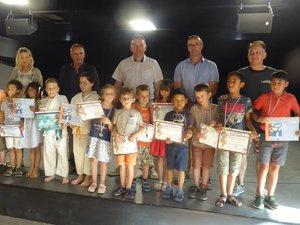Les jeunes karatékas fiers de montrer leur diplôme à leurs parents.